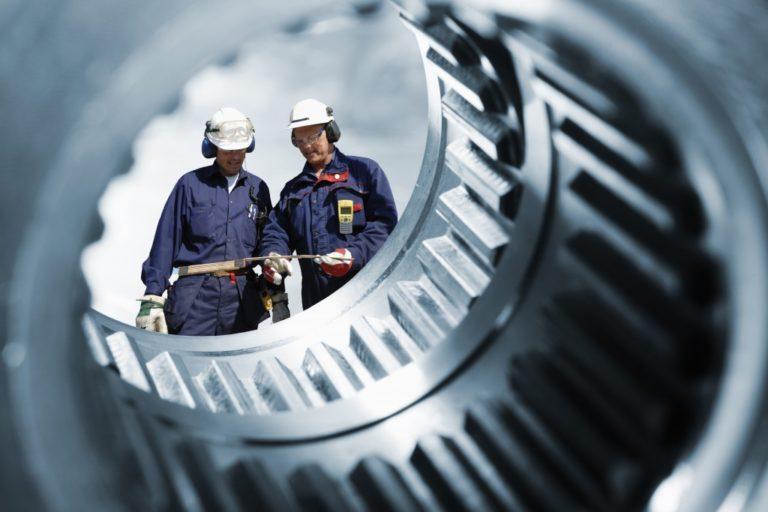 Two engineers seen through a cogwheel
