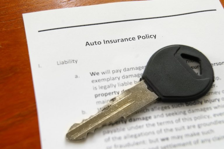 closeup of car key and auto insurance policy