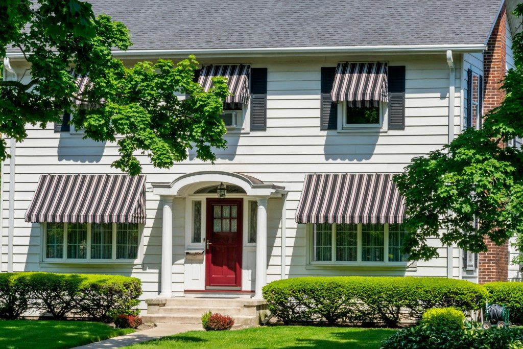 Front view of a traditional colonial home with a red door and awnings