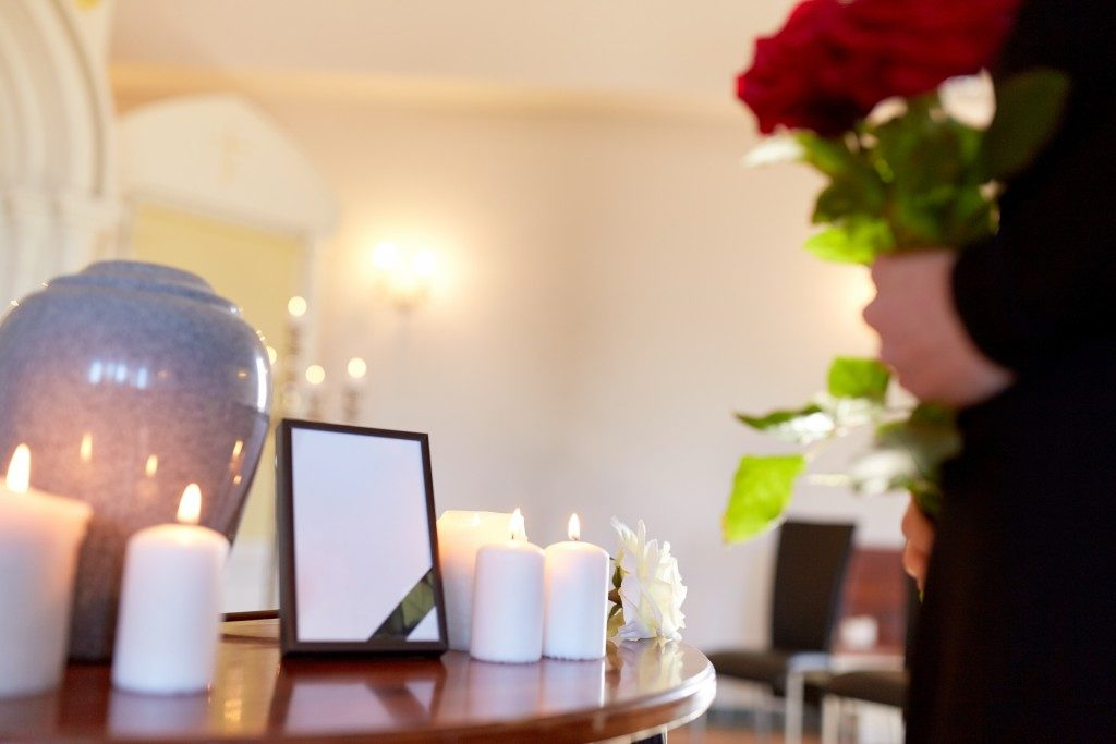urn next to candles and picture frame