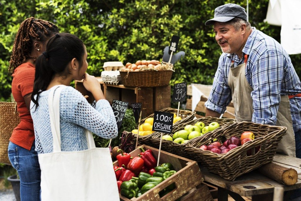fruit vendor talking to two girls