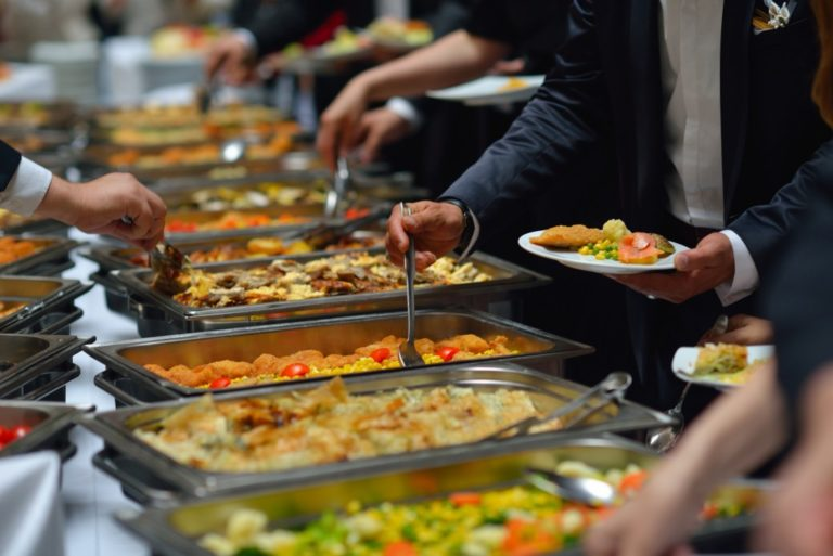people getting food from a catering buffet