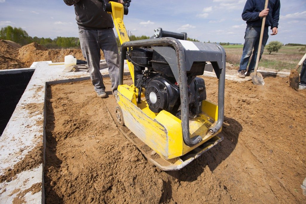 worker using a compactor
