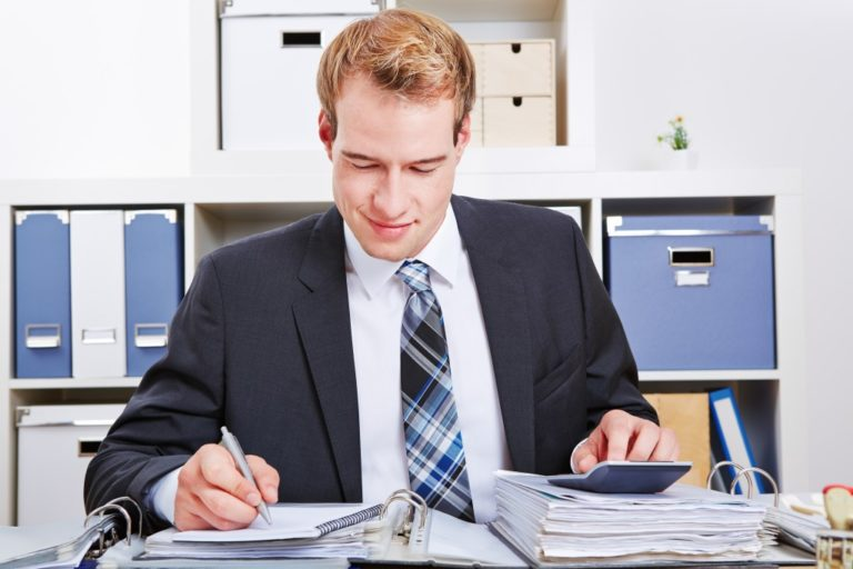 Accountant doing financing in the office with a calculator for a tax audit
