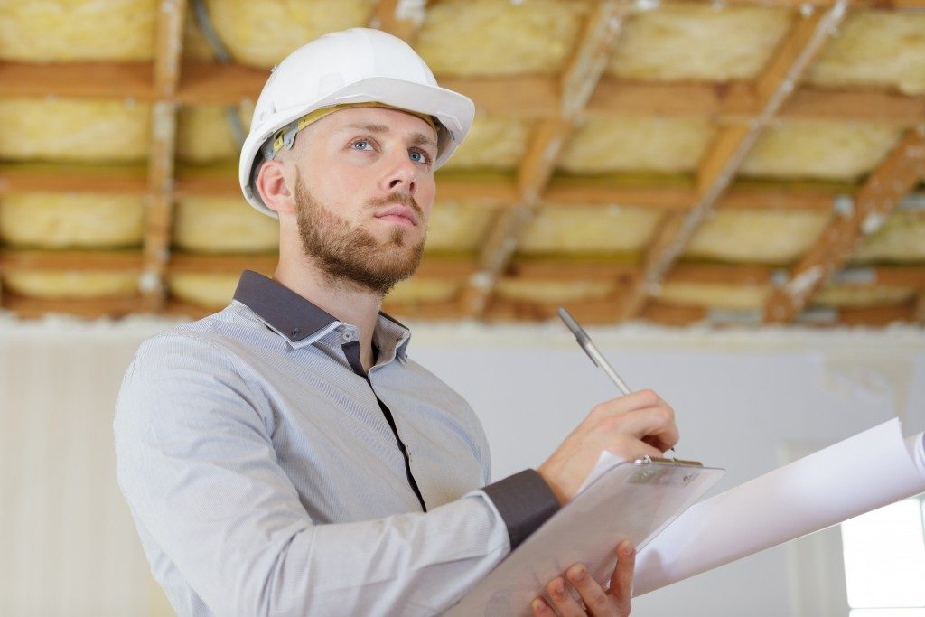 Employee wearing a hard hat while holding a clipboard