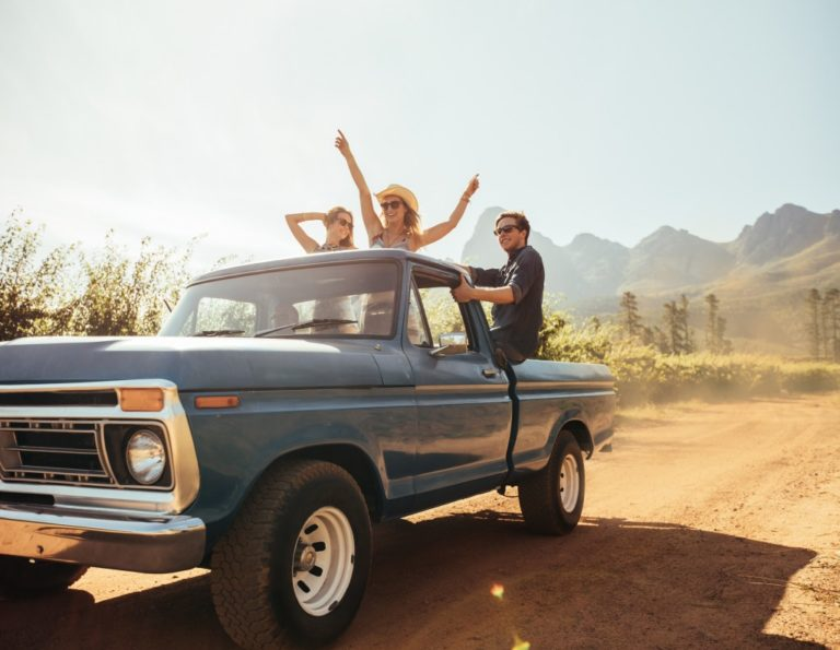 Friends riding the back of a pickup