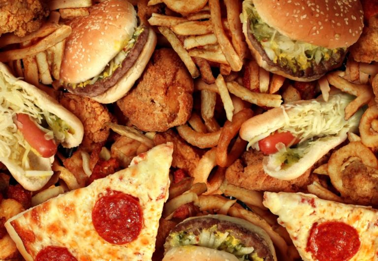 Fast food concept with greasy fried restaurant take out as onion rings burger and hot dogs with fried chicken french fries and pizza