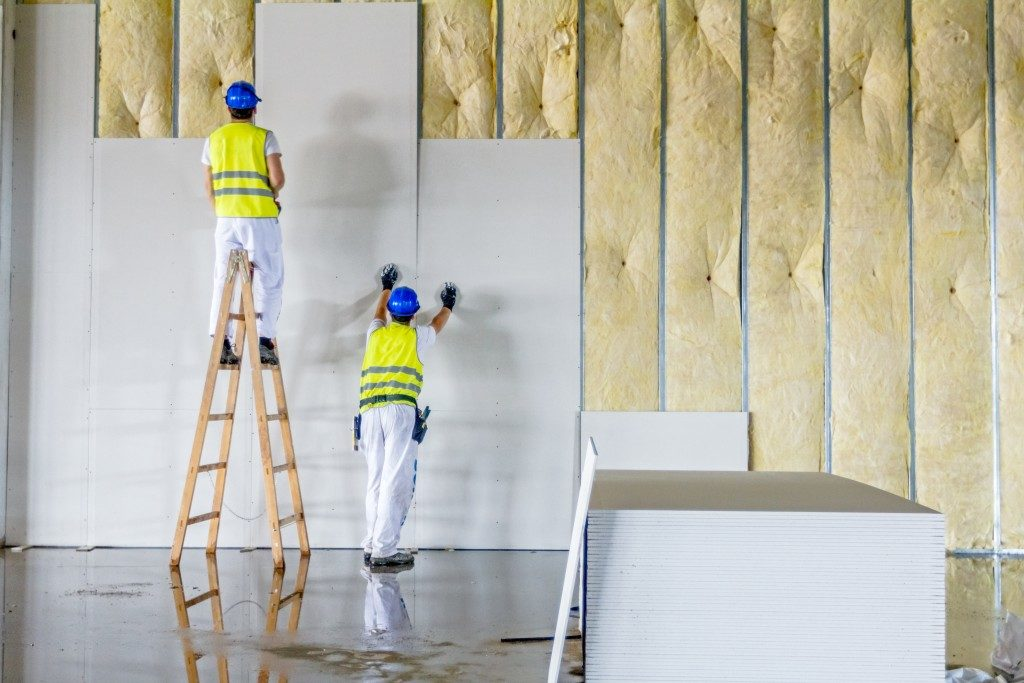 Two workers placing plaster on wall