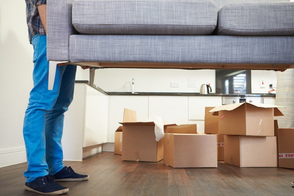 Man carrying sofa into a new home