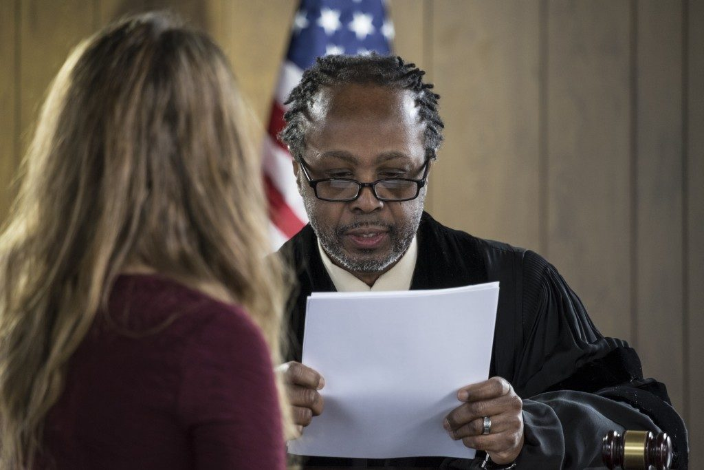 Judge reading document in front of suspect