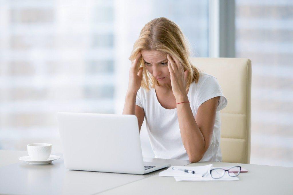 Woman experiencing a headache while working