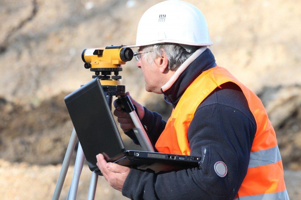 man holding a laptop while land surveying