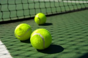 Bright greenish, yellow tennis balls on freshly painted cement court