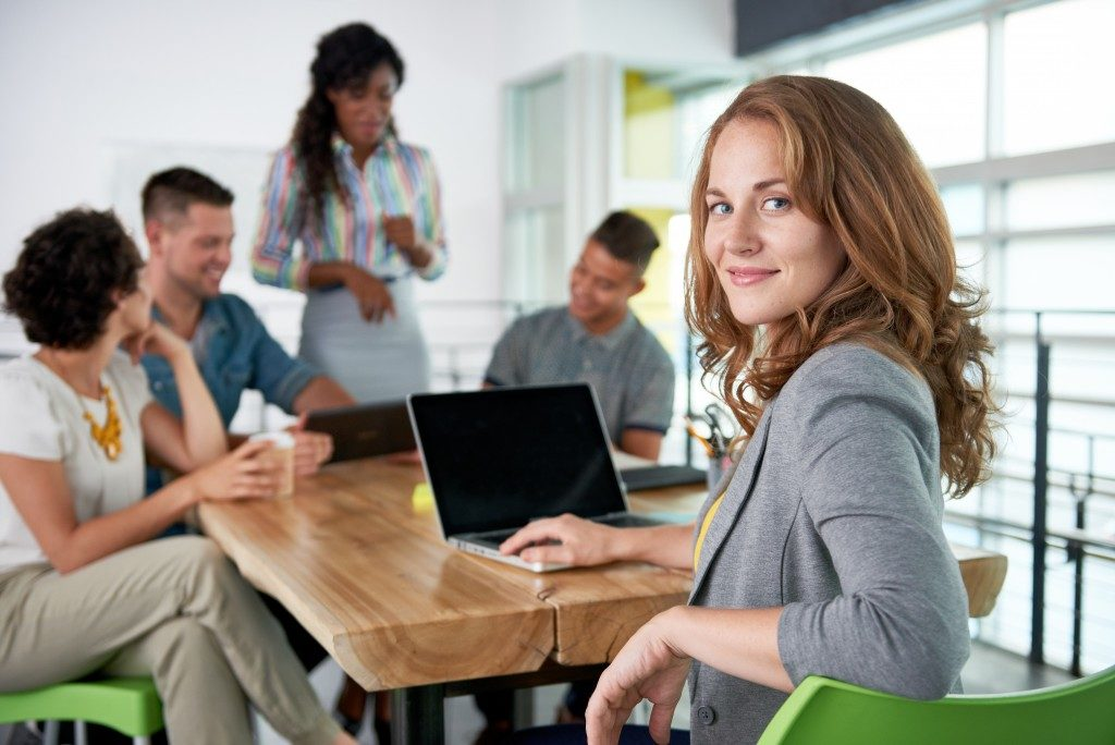 Image of a successful casual business woman using laptop during meeting