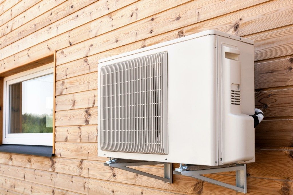 Exterior airconditioning unit mounted on wooden wall