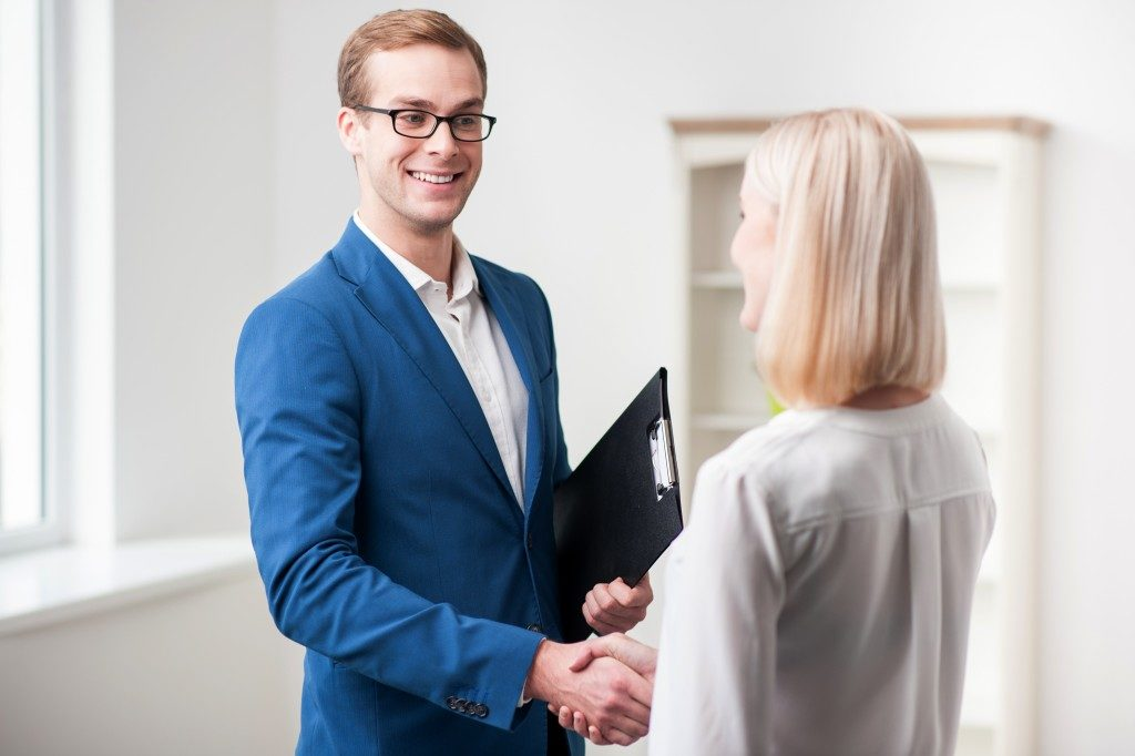 Real estate agent handshaking client