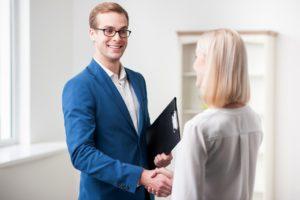 Real estate agent handshaking client