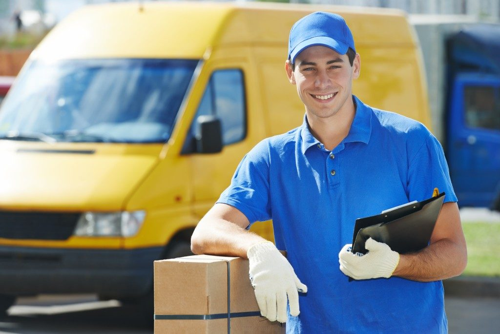 deliveryman with package and delivery van at the back