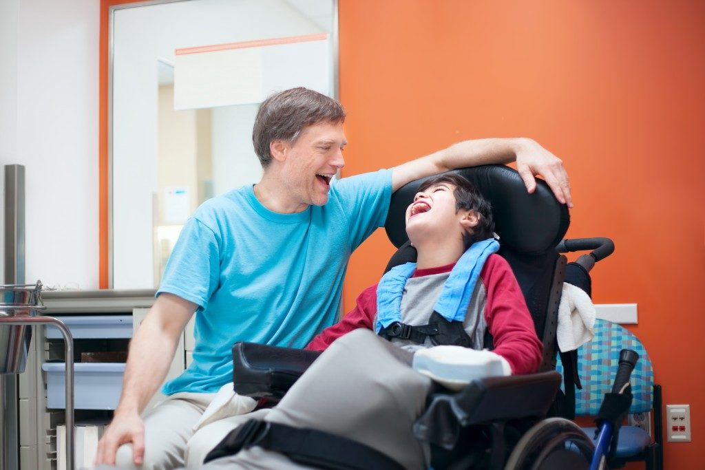father laughing with his child with disability