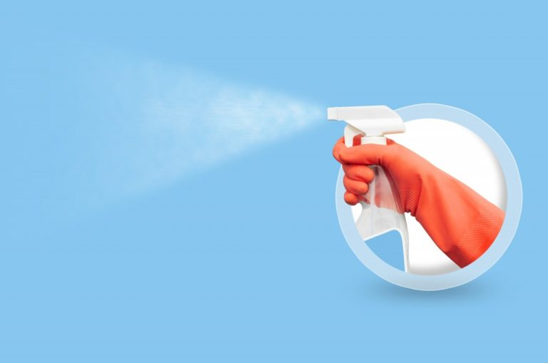 Spray bottle with hands in gloves on blue background