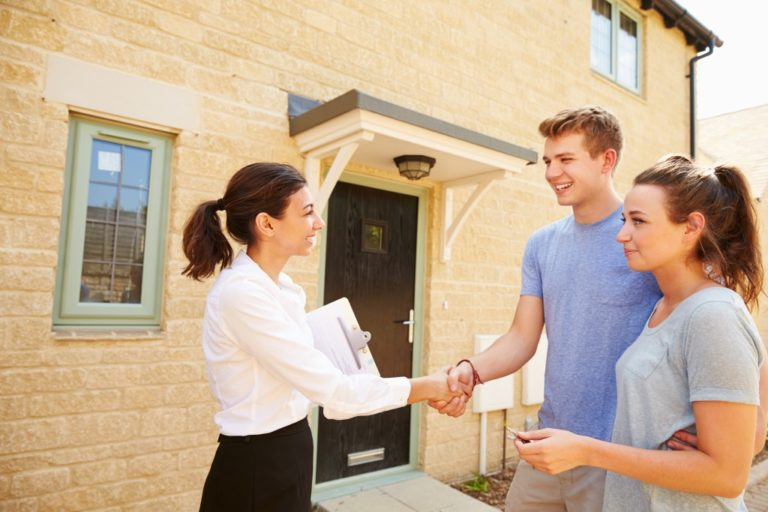 Couple shaking hands with the real estate agent