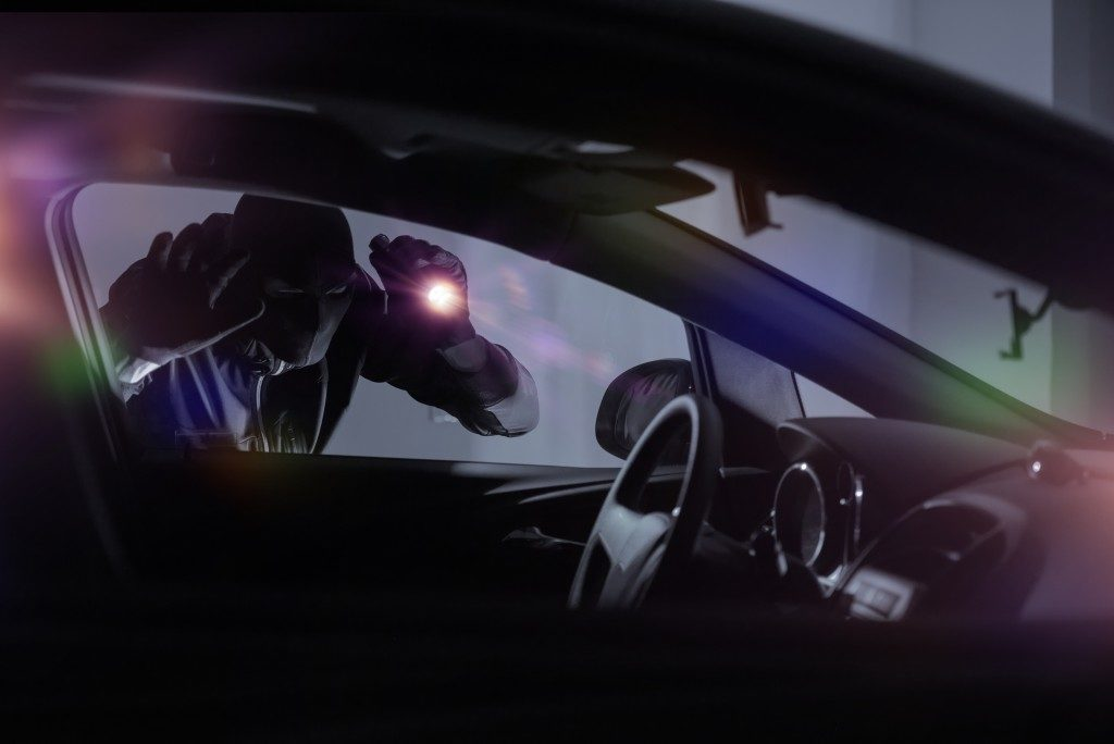 Car Robber with Flashlight Looking Inside the Car.
