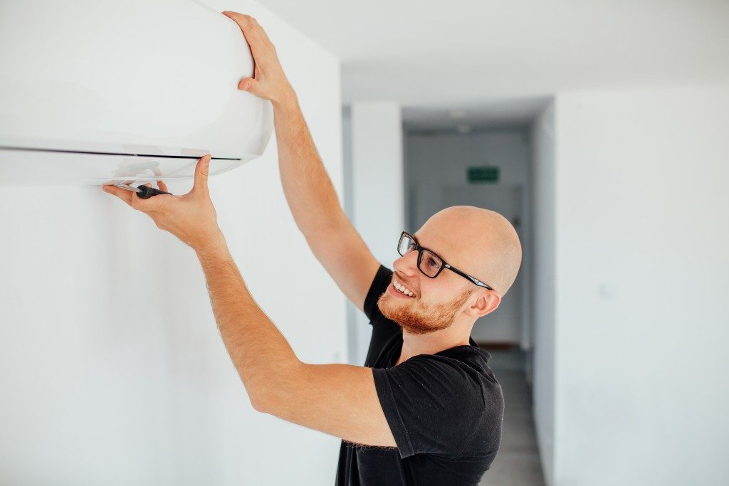 man adjusting the air conditioner