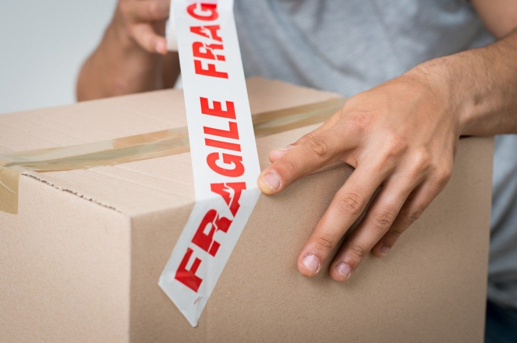 man placing fragile tape on the box
