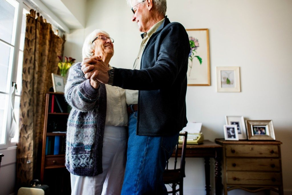 senior couple dancing in the living room