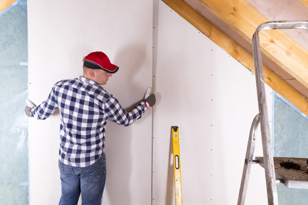 man installing dry wall