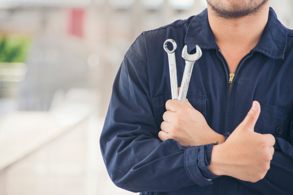 person holding two wrenches