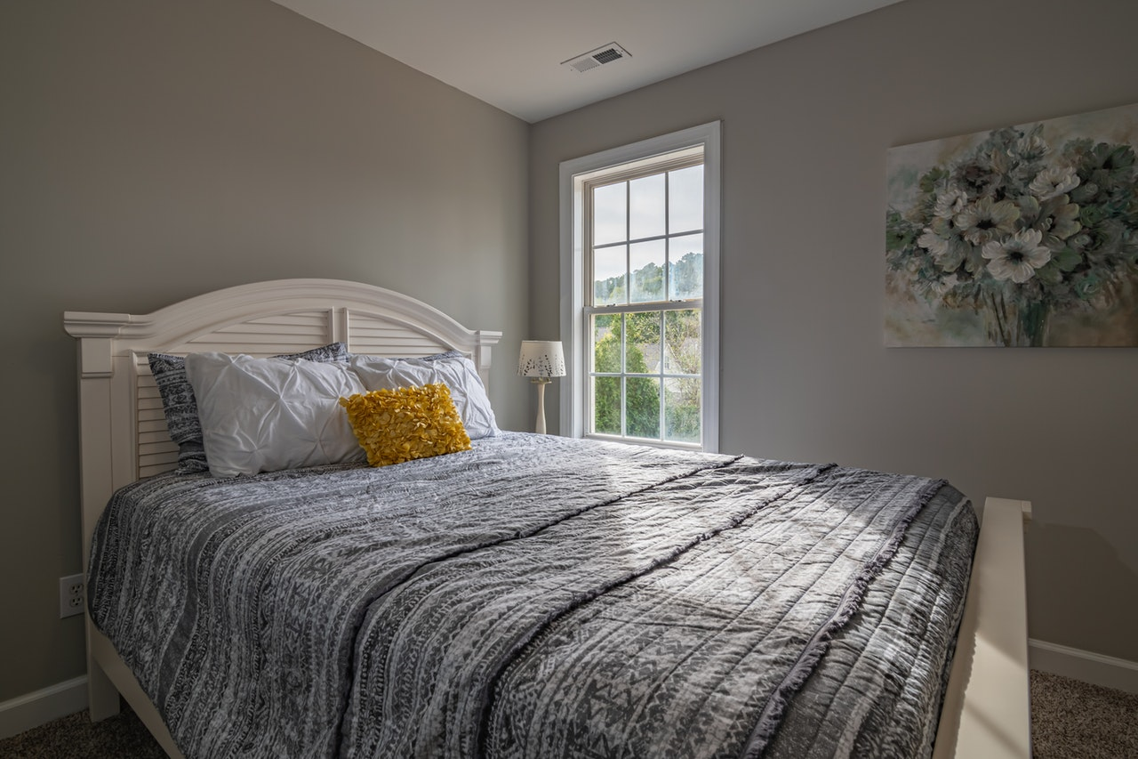 a tidy bed next to a window