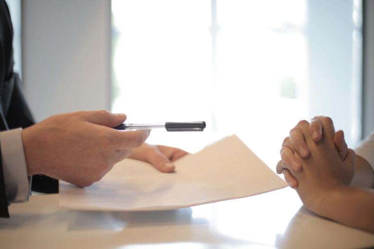 person handing over paper and pen