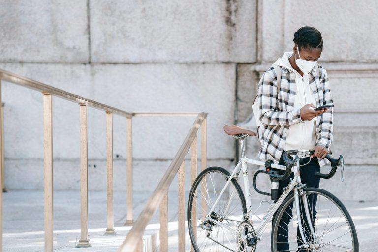 walking bike holding phone wearing facemask