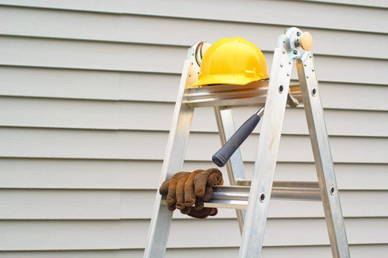 helmet, gloves, and hammer on a ladder